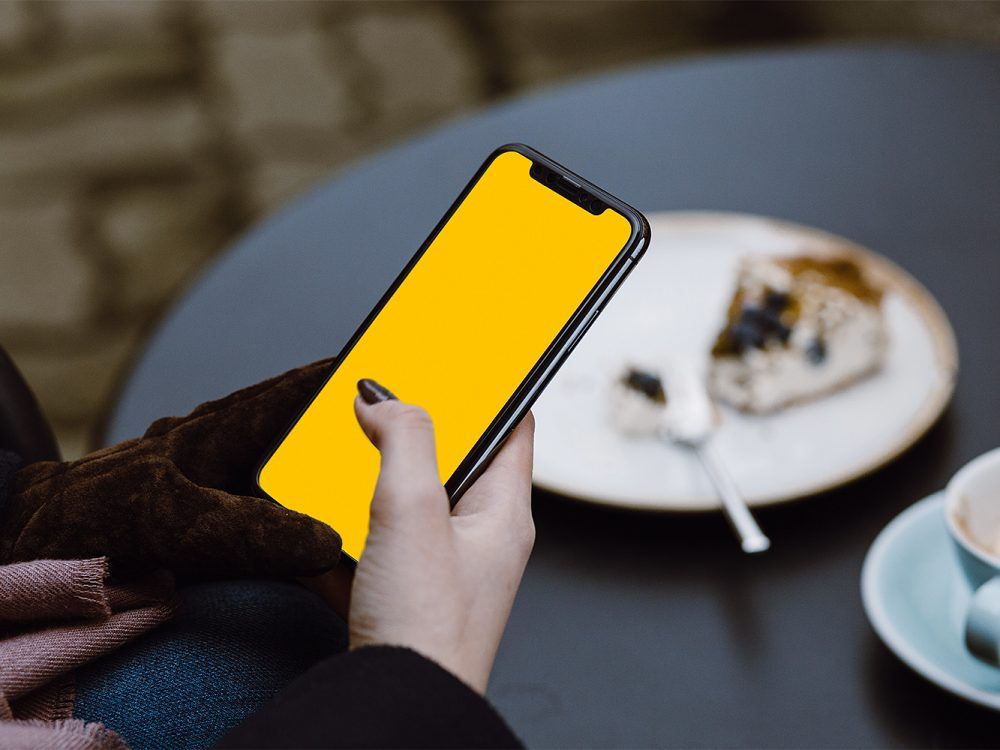 Woman at Cafe with iPhone X in Hand Mockup