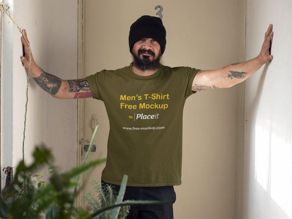 Mockup of a Tattooed Man Wearing a T-Shirt Indoors